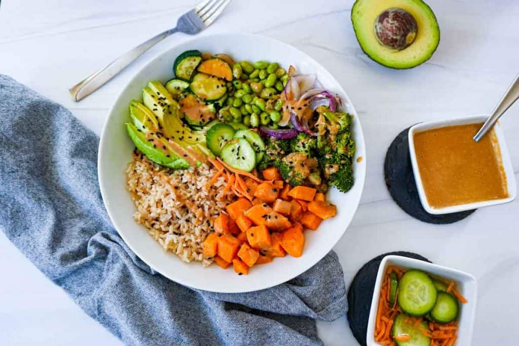 Roasted vegetable bowl with peanut sauce and brown rice.