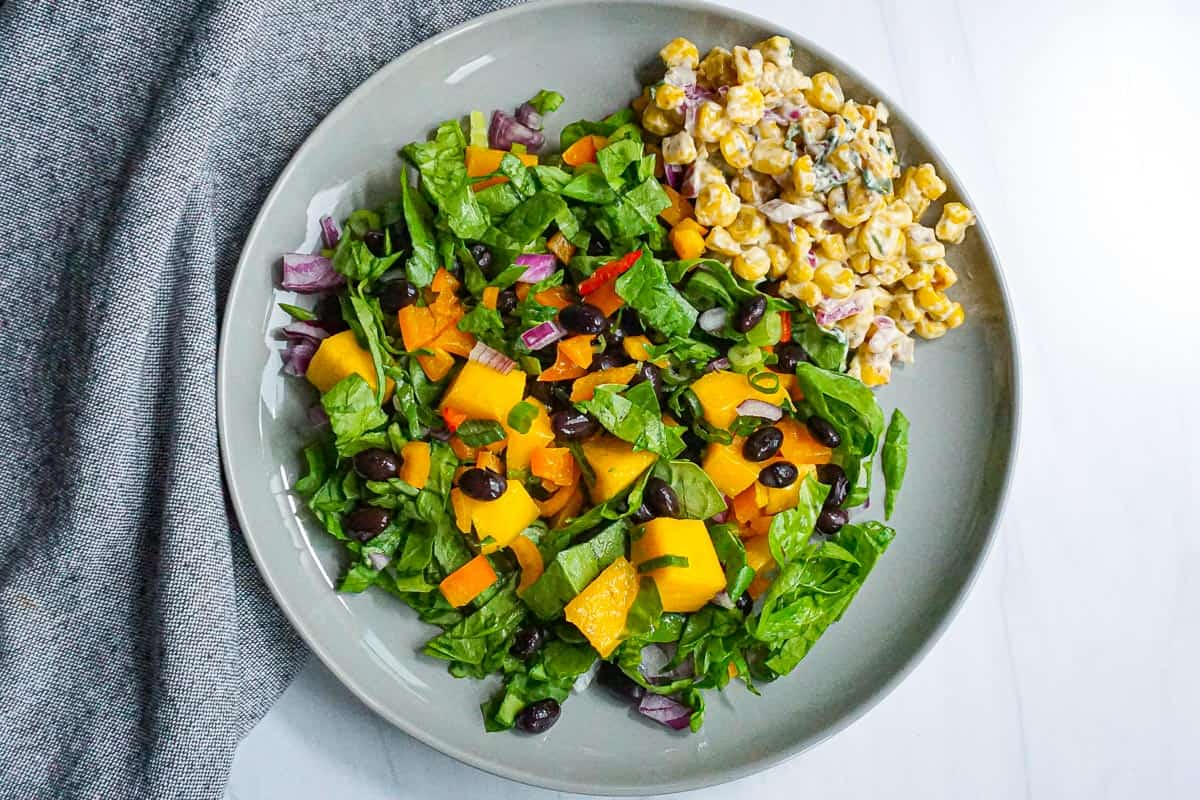 plated black bean and mango salad with side of esquites