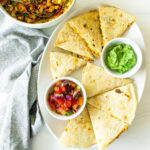 plated crumbled tempeh quesadillas with avocado sauce and pico