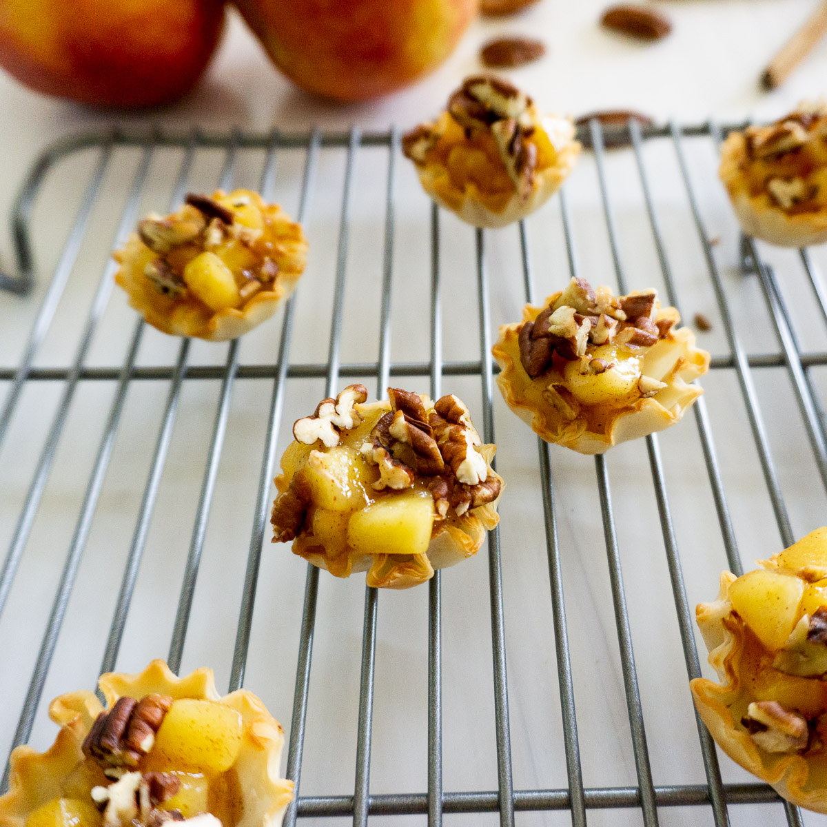 apple pie filling in phyllo shells topped with pecans
