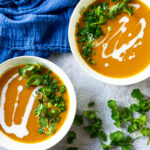 Two bowls of Thai Sweet Potato and Lentil Soup with scallions and cilantro