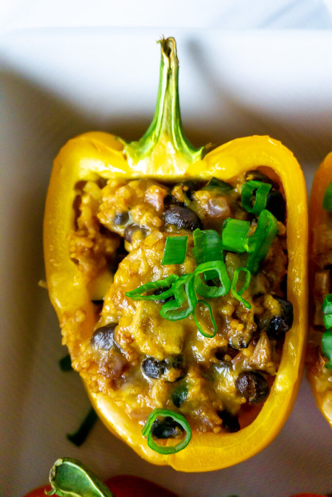 vegetarian stuffed bell peppers with couscous, black beans, cheese, and seasonal vegetables