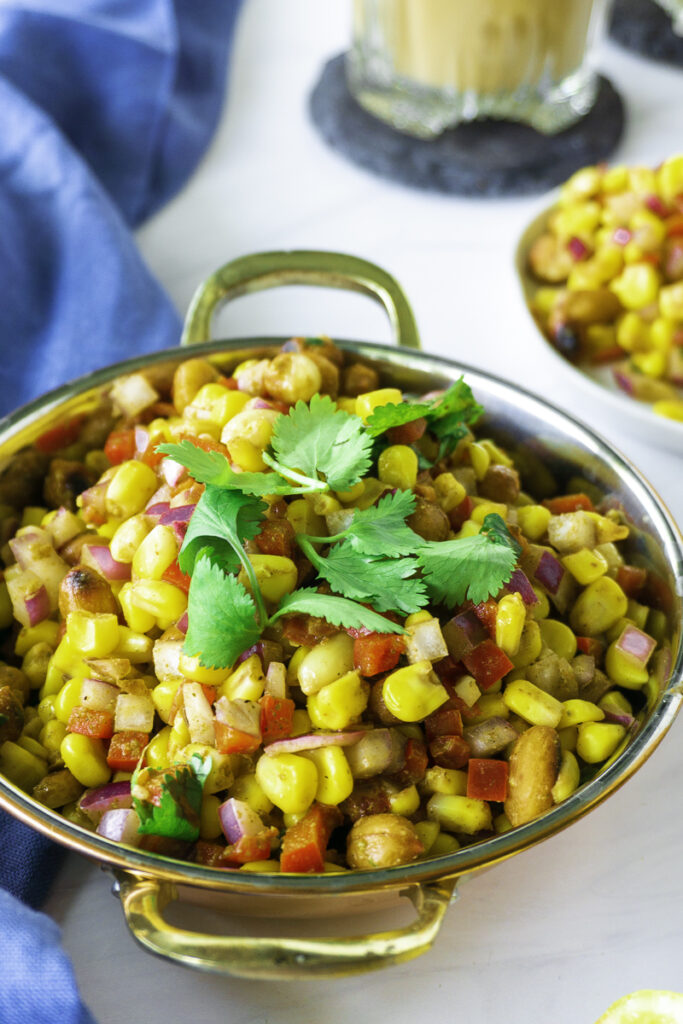 Corn chaat with peanuts, bell peppers, onions, masala, and topped with cilantro