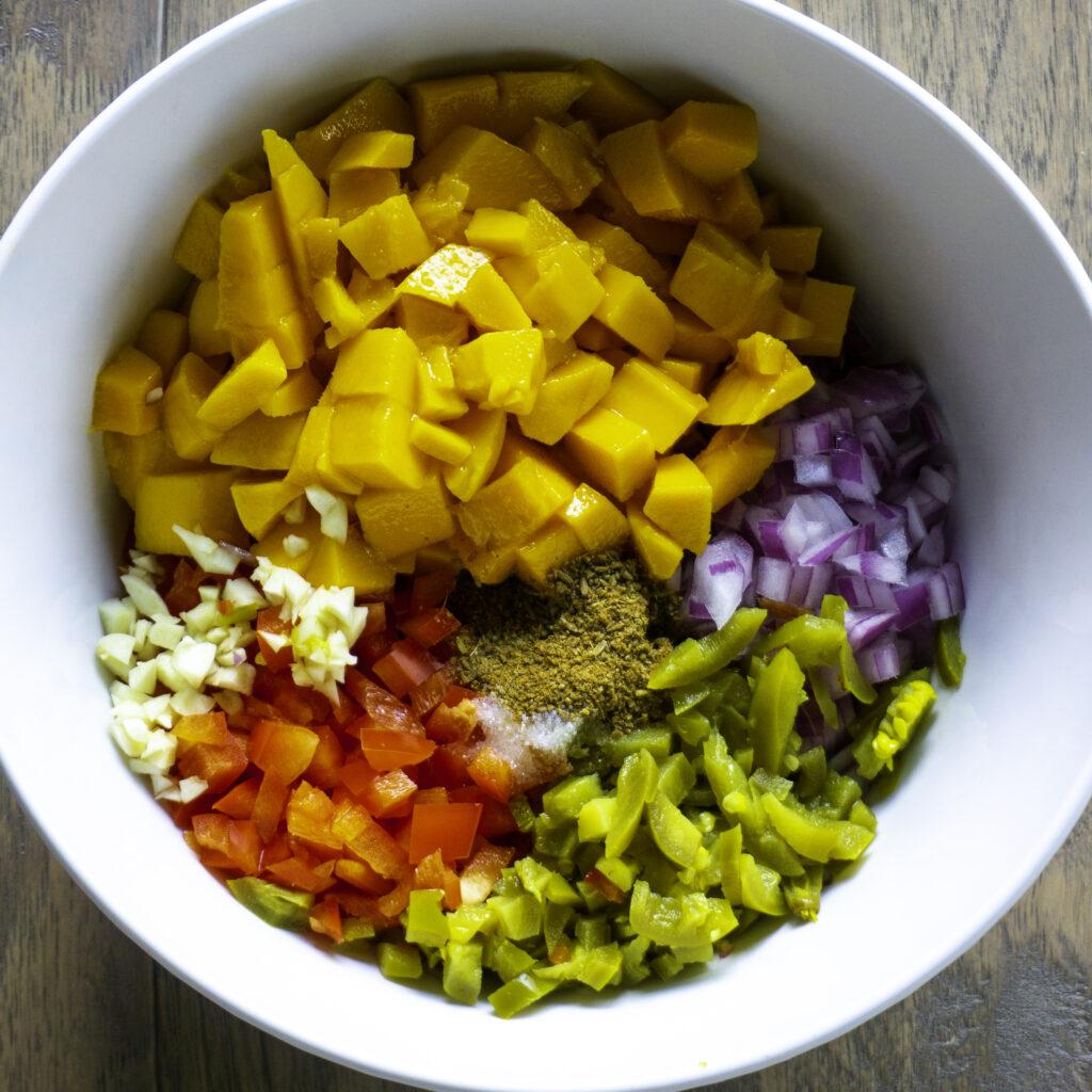 mango salsa ingredients: mango, garlic, red onion, cumin powder, red bell peppers, pickled jalapenos