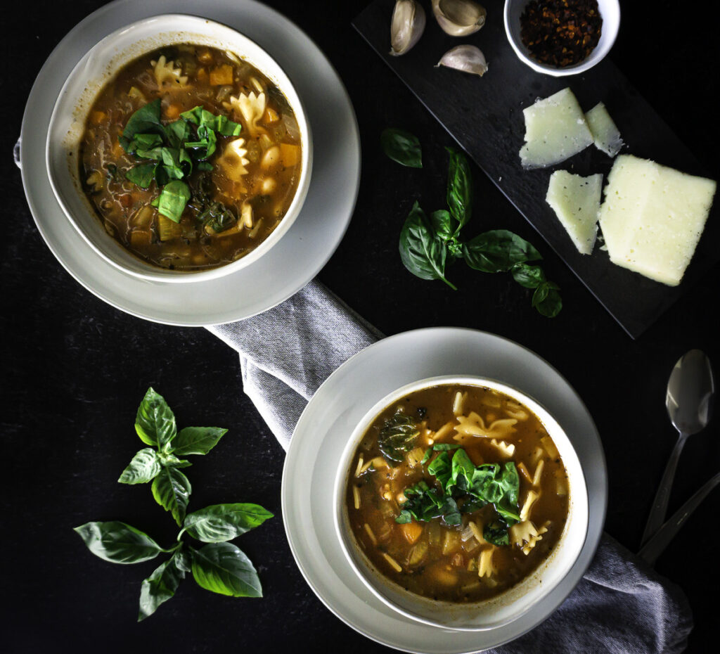 minestrone soup served with spinach, basil