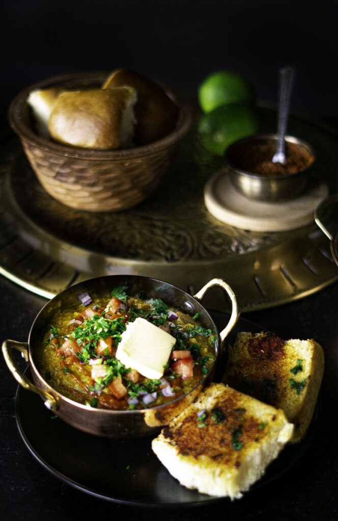 pav bhaji served with toasted bread and cilantro, onion, and tomato garnishing