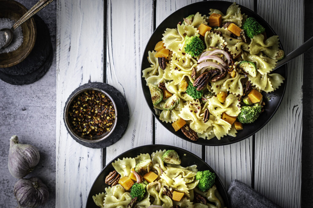 farfalle pasta with sweet potatoes, onions, brussels sprouts, pecans, and broccoli